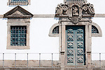 An aqua door and windows bordered with stone on a white building in Porto, Portugal.
