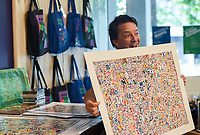 NWA Democrat-Gazette/CHARLIE KAIJO Guest artist, Michael Albert holds up an example of his art work during a drop-in art making class, Sunday, July 7, 2019 at Crystal Bridges Museum in Bentonville. <br /> <br /> Guest artist, Michael Albert, showed guests how to make art using upcycled cardboard from discarded consumer packaging. The New York native is on a multi-state tour.