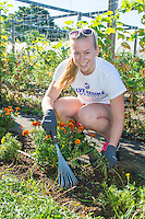 Olivia Alcott,'20, rakes weeds around the flower beds at the Methodist Community Gardens in Middletown while taking part in the Salve Regina Service Plunge.