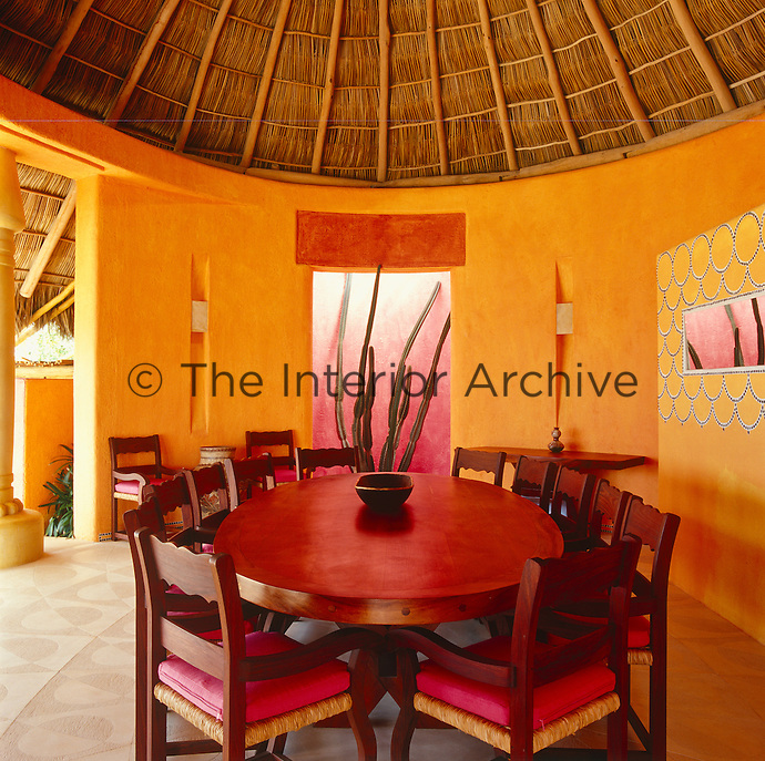 The colourful dining room opens onto a terrace and is furnished with an oval-shaped wooden table and chairs with pink squab cushions