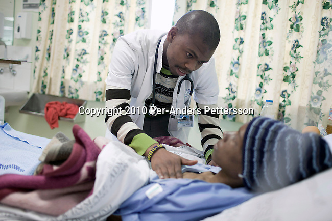 CAPE TOWN, SOUTH AFRICA - OCTOBER 21: Medical student Lwando Mpotulo (c), age 23, examines a patient in a ward at GF Jooste hospital on October 21, 2010, Cape Town, South Africa. GF Jooste is located in Mannenberg, an area with lots of gang violence and the hospital is the busiest ER hospital in the Western Cape province. Lwando and fellow students do the round with patients with the regular hospital staff in the morning. He is lucky to be able to study as a doctor at UCT, University of Cape Town but he struggles academically and and it will take 8 years instead of 6 to graduate. (Photo by Per-Anders Pettersson/Getty Images)