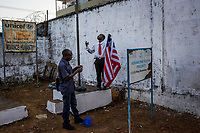 MONROVIA, LIBERIA - FEBRUARY 18: A caretaker and a teacher attempt to raise the Liberian flag, on the third day of school, since schools closed 6 months ago due to the Ebola outbreak, at the C.D.B. King Elementary School on February 18, 2015 in Monrovia, Liberia. Though Ebola cases have receded into the single digits in Liberia, lingering fear and a depressed economy have dampened the turnout at schools. Many have yet to reopen, having failed to meet the minimum requirements put in place to prevent the transmission of the virus. Many of those that have reopened – like C.D.B. King, which, though located in the center of the capital, lacks electricity and running water, and has only a few toilet stalls for a student population that numbered 1,000 before Ebola — are struggling.<br /> Daniel Berehulak for The New York Times
