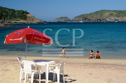 Buzios, Rio de Janeiro, Brazil. Family with two children on Forno beach with plastic table and chairs with red Hollywood sunshade