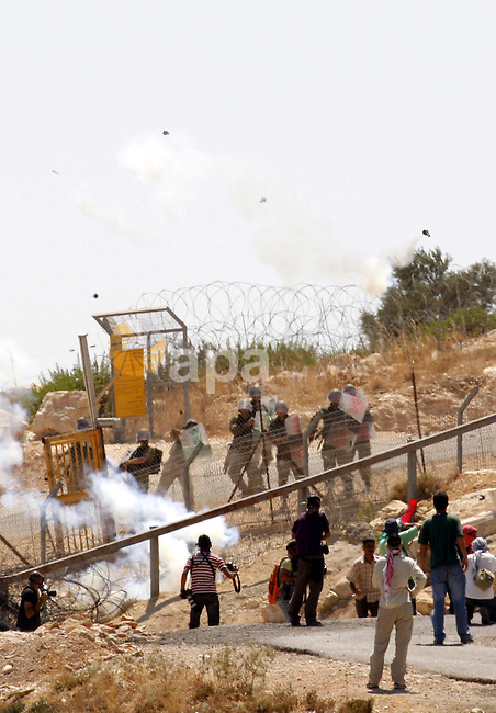 Palestinian and foreign protestors run away from  tear gas threw by Israeli soldiers during a demonstration against Israel's controversial separation barrier in the West Bank village of Bilin near Ramallah on July 24, 2009. Photo by Nedal Shtieh