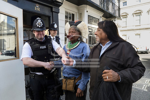 11 June 2014. Kayapo Chiefs Raoni Metuktire and Megaron Txucarramae during their visit to London. The chiefs shake hands in greeting with a policeman in front of Clarence House.