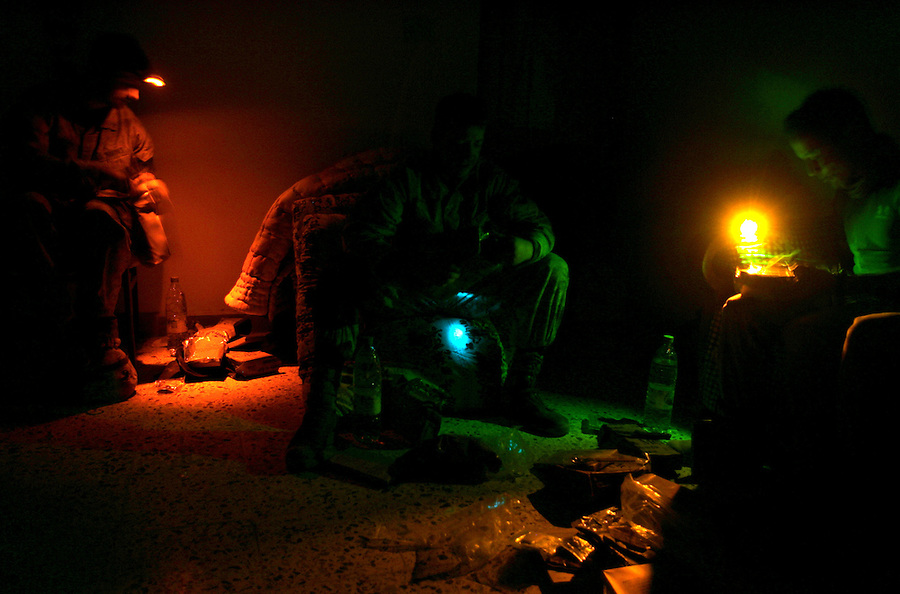 Restricting light as much as possible, Marines from Golf Co. 2nd Battalion 1st Marines searches through their Meals-Ready-Eat by the light of small colored flashlights at the end of the fourth day of Operation Steel Curtain, an operation to clear Husaybah (a city on the Iraq-Syrian border) of insurgents on Mon. Tues. 8, 2005.