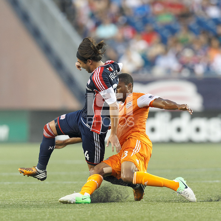 In a physical match, Houston Dynamo midfielder Ricardo Clark (13) takes out New England Revolution midfielder Lee Nguyen (24) as they battle for the ball. In a Major League Soccer (MLS) match, Houston Dynamo (orange) defeated the New England Revolution (blue), 2-1, at Gillette Stadium on July 13, 2013.