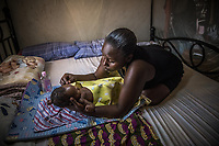 Uganda, Seeta. Ann Nankya has the Wowsolar power system that she uses to charge her radio and lights. She uses the light to bath her baby in the evening.