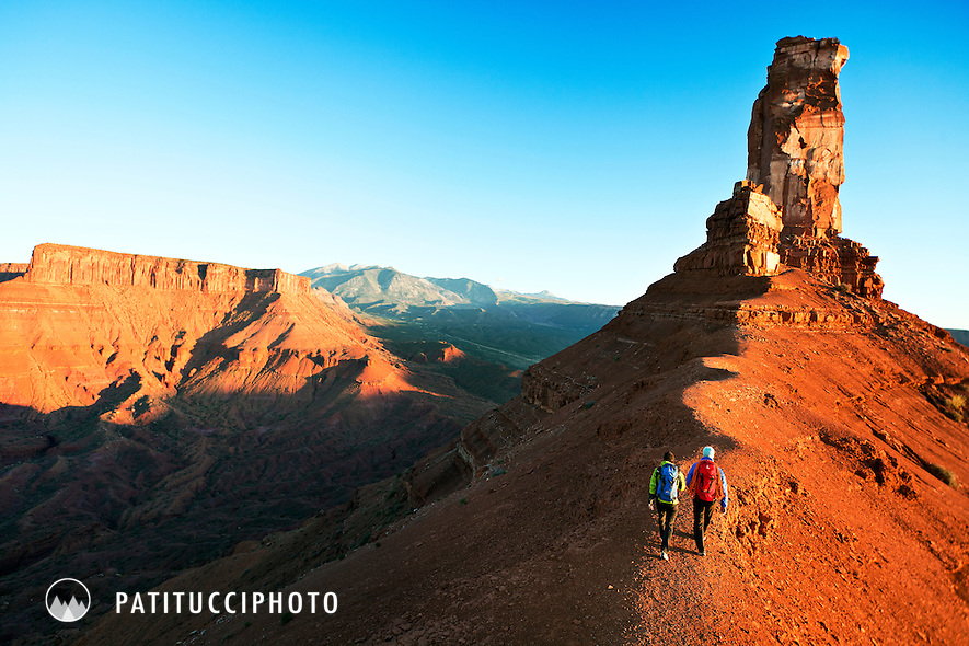 Two climbers walking beneath Castleton Tower high above Castle Valley, Utah
