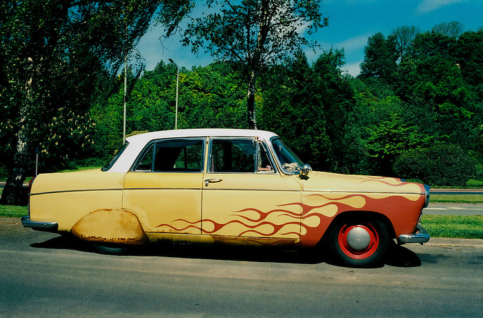 An old car with a flame custom paint job parked on a residential street in Brighton,England. 2001.