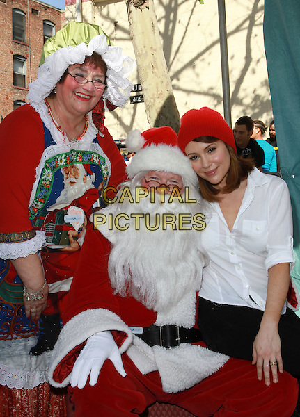 ALYSSA MILANO with Santa and Mama Claus.Christmas Eve For Homeless Served at Los Angeles Mission held At The Los Angeles Mission, Los Angeles, CA, USA..December 24th, 2010.half length red beanie hat white shirt sitting lap costume .CAP/ADM/KB.©Kevan Brooks/AdMedia/Capital Pictures.