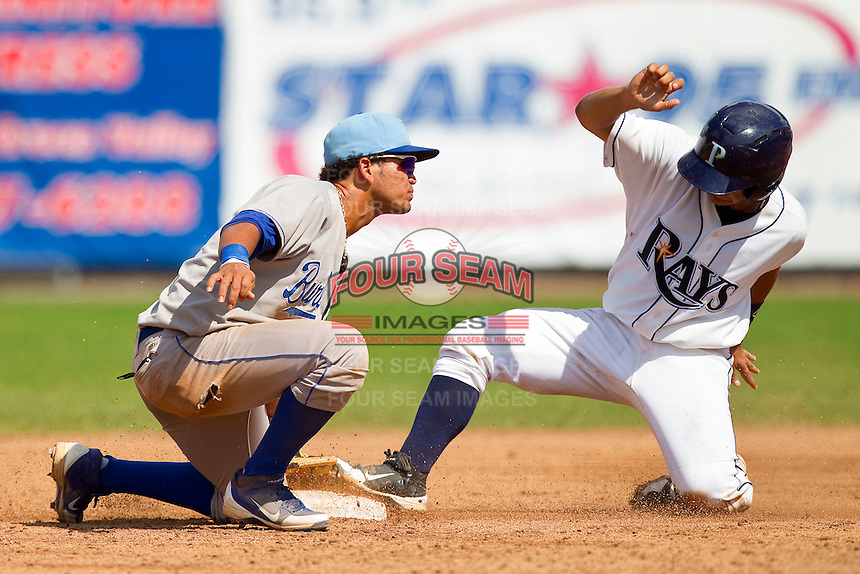 Burlington Royals shortstop Humberto Arteaga (13) puts the tag on Omar Narvaez (24) of the Princeton Rays as he is caught trying to steal second base at Hunnicutt Field on July 15, 2012 in Princeton, West Virginia.  The Rays defeated the Royals 3-1 in game two of a double header.  (Brian Westerholt/Four Seam Images)
