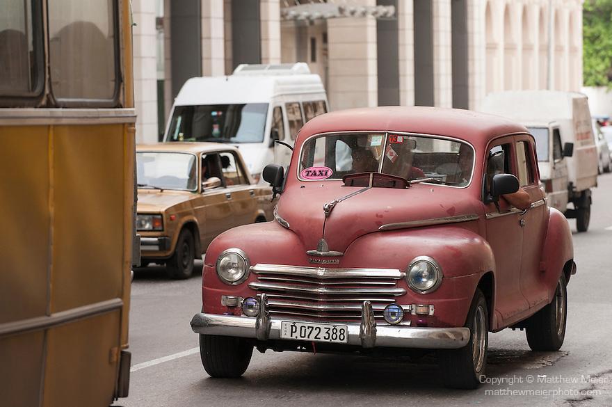 Havana, Cuba; a red, classic 1948 Plymouth car driving down the street in Havana
