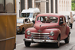 Havana, Cuba; a red, classic 1948 Plymouth car driving down the street in Havana