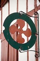 Europe/France/Aquitaine/64/Pyrénées-Atlantiques/Bidart : Enseigne en forme de croix basque  sur une des maisons de la place du village
