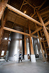 A staffer walks past one of the massive vats inside the Chuko distillery in Naha, Okinawa Prefecture, Japan, on May 20, 2012. Photographer: Robert Gilhooly
