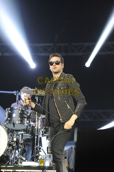 Tom Meighan.Kasabian performing at the o2 Arena, Greenwich, London, England..31st December 2011.in concert on stage live gig performance music half length black jacket top sunglasses shades jeans denim  .CAP/MAR.© Martin Harris/Capital Pictures.