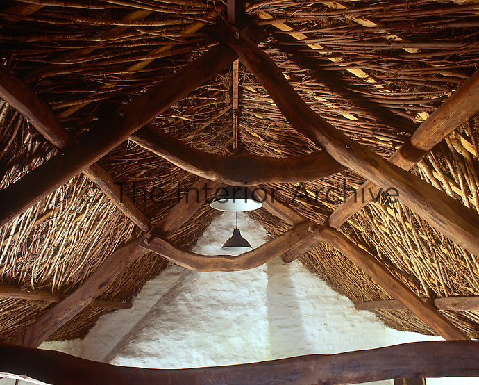 The underthatch is defined by a herringbone pattern of woven hazel and the sinuous curves of the oak beams