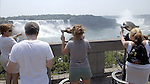 Niagara Falls, Ontario, Canada - 01 August 2006---Tourists / visitors overlooking Niagara River with the Horseshoe Falls (ri), on the Canadian side and the American Falls (le), on the United States' side---nature, landscape, people---Photo: © HorstWagner.eu