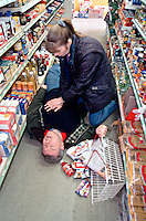 A man out shopping falls in the aisle of a supermarket having suffered a heart attack. Another shopper realizes what is happening and performs CPR on him. This image may only be used to portray the subject in a positive manner..©shoutpictures.com..john@shoutpictures.com