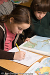 Elementary school Grade 5 male and female students working on geography social studies assignment working with map book horizontal