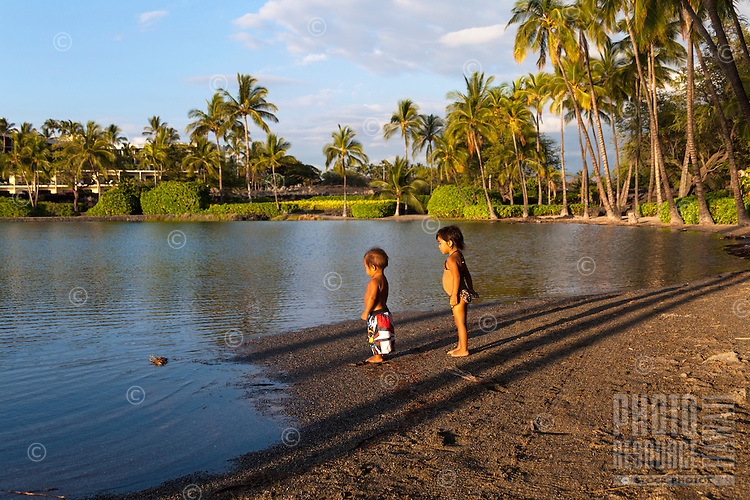 Young children stand by the historic fishpond at 'Anaeho'omalu Beach, Waikoloa, Big Island.