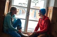 A couple sits inside the Bella Vista Hut watching it snow during the Öztal ski tour, Austria