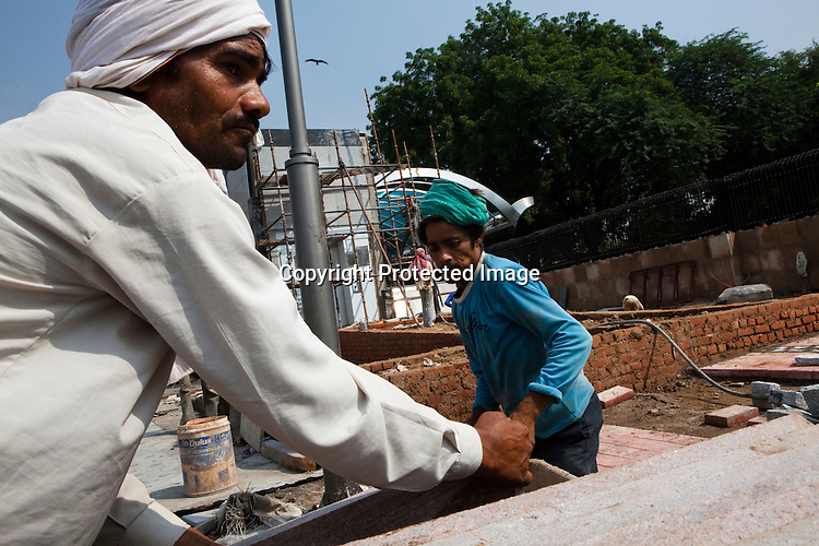 Construction workers are seen working on the pavement outside the Jawahar Lal Nehru stadium in New Delhi, India.