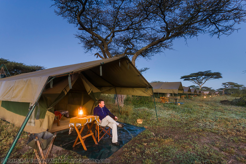 Man watches dawn approach outside a luxury mobile tented camp, Serengeti National Park, Tanzania, East Africa