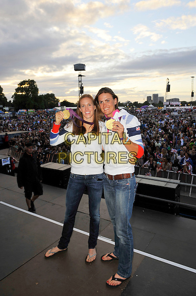 Helen Glover and Heather Stanning, Olympic Gold Medal Winners for Team GB, attending BT London Live, Hyde Park, London, England..2nd August 2012.stage full length white jacket jeans denim winners rowing rowers.CAP/MAR.© Martin Harris/Capital Pictures.