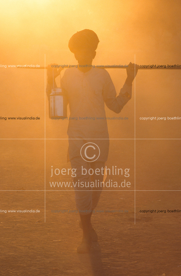 INDIA Rajasthan, shepherd with turban walking home to his village in the evening / INDIEN, Hirte mit Turban und Stock im Gegenlicht der untergehenden Sonne