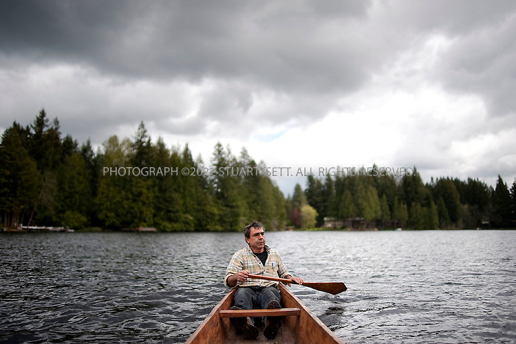 5/7/2009--Sammamish, WA, USA..John Mullen on one of the Snoqualmie tribe's dug-out canoes, on Beaver Lake. John  is employed as the Snoqualmie tribe's master carver. Every year two dozen or so Snoqualmie Indians convene at the base of Snoqualmie Falls--a sacred tribal site-- to begin their annual Canoe Journey. This year a 100-mile voyage out into and across Puget Sound to a five-day powwow hosted by the Suquamish tribe at their reservation on the Kitsap Peninsula. Each year a different coastal or river-based Northwest tribe hosts the powwow, with dozens of other tribes paddling there celebrate their common culture and heritage. ..The Canoe Journey tradition has been instrumental in reviving an age-old Snoqualmie tribe tradition: wood carving. Needing canoes and paddles to accommodate all tribal members who want to go on the annual Canoe Journey, the tribe established a woodworking budget and secured a carving shed soon after it was re-acknowledged in 1999. These days, four tribal members, led by John Mullen (the brother of drum bearer Ray), work full-time at the shed, making dugout canoes out of old-growth red cedar trees and paddles out of big leaf maple wood, just like their forebears in centuries past. ...©2009 Stuart Isett. All rights reserved.