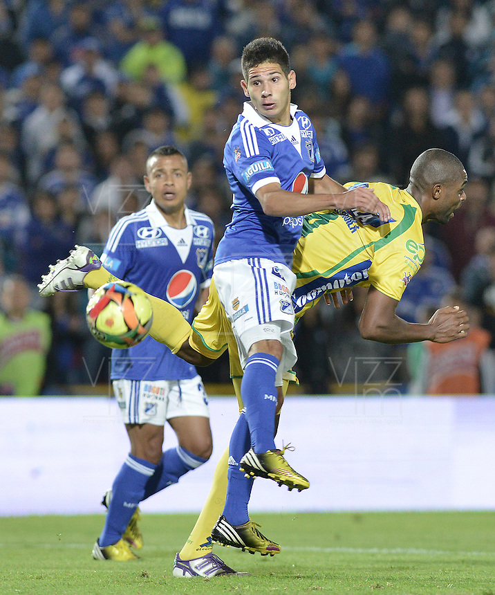 BOGOTÁ -COLOMBIA, 31-08-2013. Jonathan Agudelo (I) de Millonarios disputa el balón con Cesar Mena (D) del Huila durante partido válido por la fecha 8 de la Liga Postobón 2013-1 jugado en el estadio el Campín de la ciudad de Bogotá./ Millonarios Player Jonathan Agudelo (L) fights for the ball with Huila player Cesar Mena (R) during match valid for the 8th date of the Postobon  League II 2013 played at El Campin stadium in Bogotá city. Photo: VizzorImage/Gabriel Aponte/STR