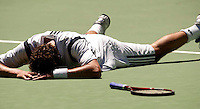 Marat Safin lies on centre court after stumbling during his match against Mario Ancic during their match at the Australian open.