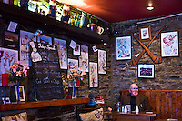 Elderly man sits alone with cup of tea and beer in traditional Irish Bar Grainne's in Timoleague, West Cork, Ireland