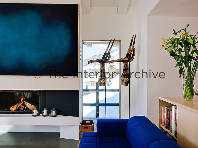 In keeping with the ultra modern interior of the chalet,  the fireplace has been enhanced with a bold piece of modern art
