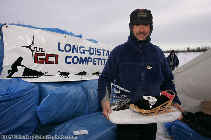 Robert Sorlie holds his trophy and gold for being the first to the half-way checkpoint, Iditarod.  Iditarod checkpoint.  2005 Iditarod Trail Sled Dog Race.