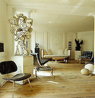 The bare wooden floorboards and white wood panelled walls of the living room create a neutral canvas for Mechiche's collection of period and modern furniture and sculpture by Jean Dubuffet, Joseph Beuys, Pierre Soulages and Cesar and Jean Arp