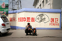 A man and his child in a town on the Qinghai-Tibetan Plateau, Qinghai Province. China. 2010