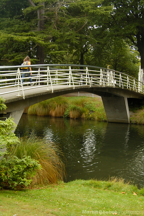 Woman crossing a bridge over the Avon River, Christchurch Botanic Gardens, Christchurch, New Zealand