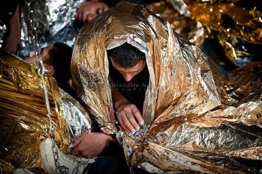 Lampedusa, 11 Ottobre, 2008. Un immigrato appena tratto in salvo su una barca della Guardia Costiera di Lampedusa.<br /> Immigrants saved by the Italian Coast Guard