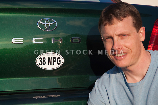 Portrait of mid adult man by a 38 miles per gallon fuel efficient Toyota Echo car. Sticker from MPG Stickers (mpgstickers.com), a grassroots, nonprofit campaign which aims to accelerate the adoption of fuel efficient vehicles in the United States. California, USA. Property released from mpgstickers.com.