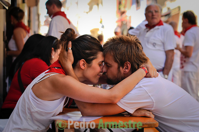 A couple kisses during San Fermin Festival, on July 14, 2012, in Pamplona, northern Spain. The festival is a symbol of Spanish culture that attracts thousands of tourists to watch the bull runs despite heavy condemnation from animal rights groups.  (c) Pedro ARMESTRE