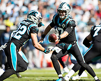 CHARLOTTE, NC - NOVEMBER 3: Kyle Allen #7 of the Carolina Panthers hands the ball off to Christian McCaffrey #22 during a game between Tennessee Titans and Carolina Panthers at Bank of America Stadium on November 3, 2019 in Charlotte, North Carolina.