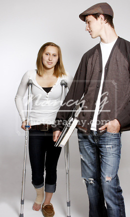 A young boy holding a book and laptop for a young girl with an injured foot on crutches