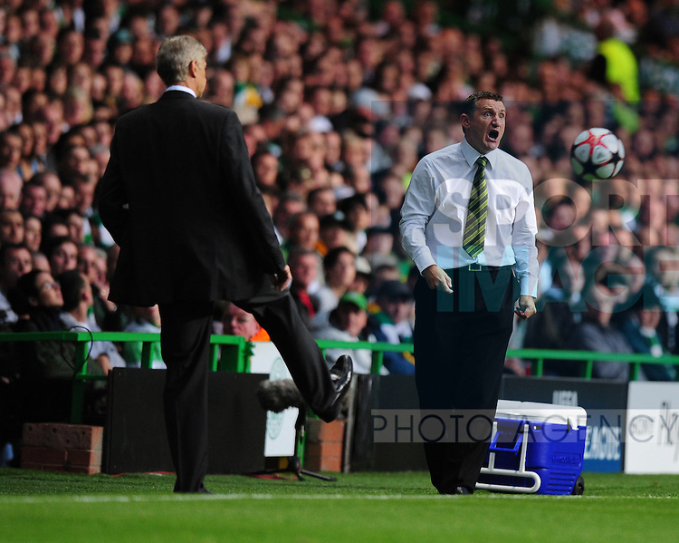 Tony Mowbray manager of Celtic shouts instructions as Arsenal manager Arsene Wenger kicks the ball back into play