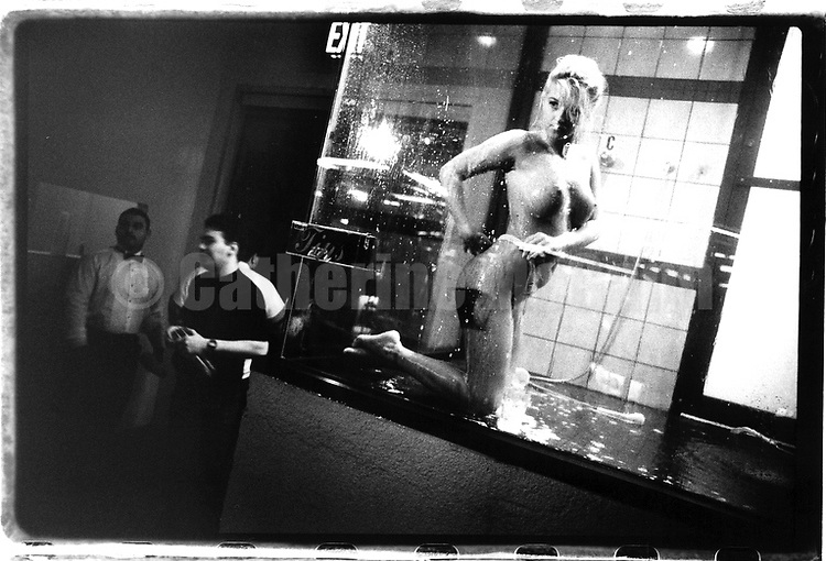 1992:  A stripper takes a shower in an enclosed shower booth at Goldfinger's strip club in New York City.