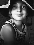 A young girl smiling wearing a floppy hat looking directly at the camera