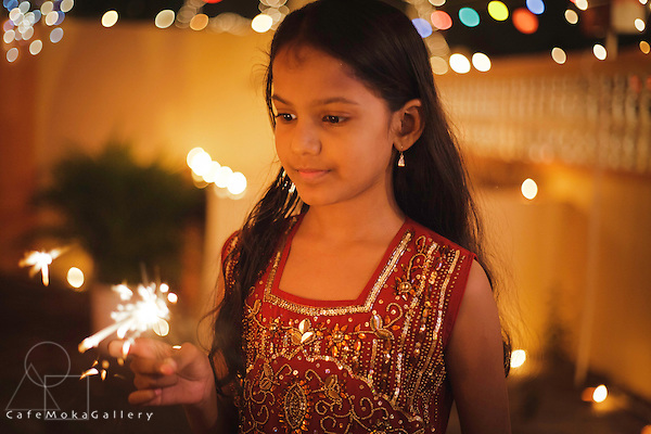 Divali, Hindu festival of light, beautiful young Indo-Trinidadian girl with a sparkler surrounded by lights