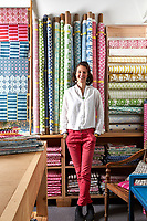 A portrait of designer Molly Mahon with samples of her fabrics in her studio.